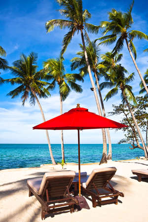 chang: Red umbrella and chairs on sand beach in tropic. Thailand, Koh Chang, Klong Prao beach Stock Photo