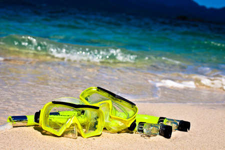 scuba mask: Two yellow snorling masks on sand on beach Stock Photo