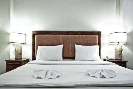 hospedaje: Interior de la habitaci�n de hotel con almohadas y luces en la noche Editorial