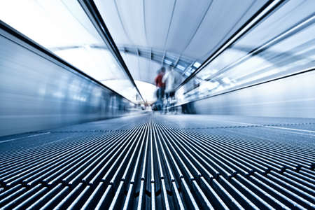 metallic stairs: Moving blue travolator in airport hall, people silhouettes move Stock Photo