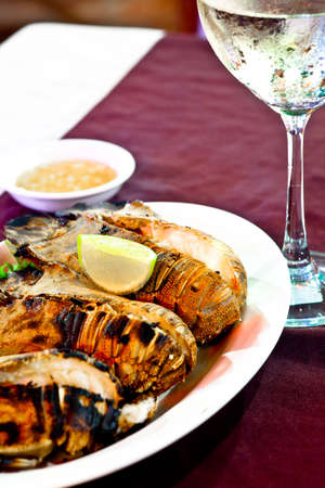 Slipper lobsters fried on grill, served with lime and wine photo