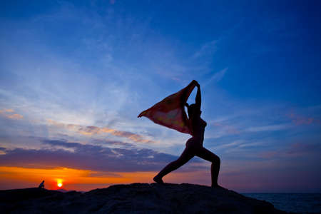 A silhouette of a women practicing yoga at sunset on beach photo