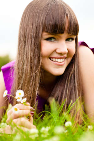 Portrait of young woman with small bouquet of  camomiles photo