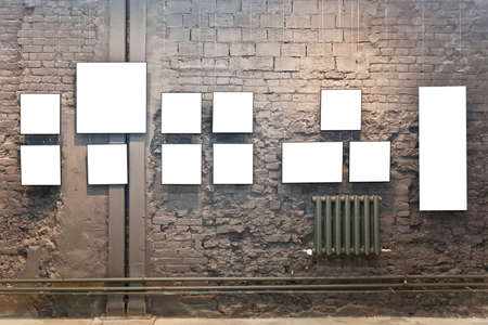 Empty frames on brown brick wall in museum Stock Photo