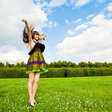teenage girl dress: Pretty smiling girl with long brown hairs on green meadow