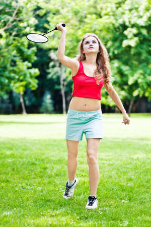 Girl in red play badminton in park photo