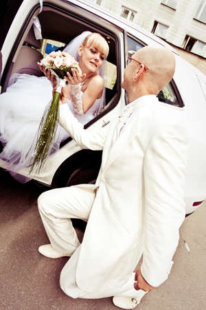 Happy young couple of bride and groom in car photo