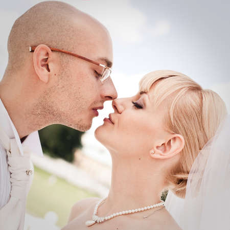 Happy young couple of bride and groom kissing in park photo