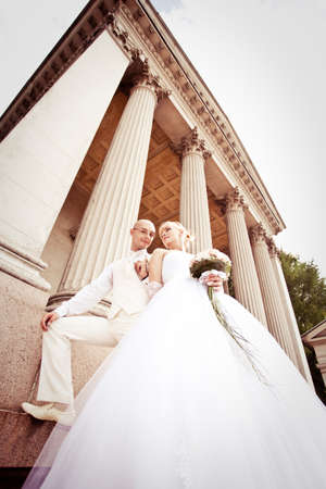 Happy young couple of bride and groom embrace near columns photo
