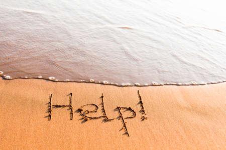 Word HELP on sand near sea wave Stock Photo - 8380018