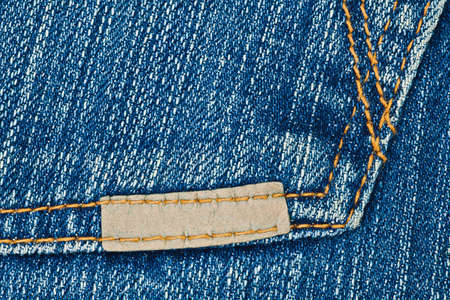 zigzagger: Blank small leather label on blue jeans