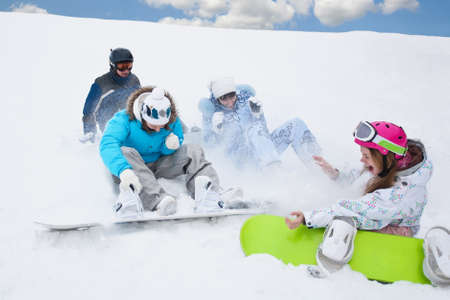 friendly competition: Snow splashes and three young girls sit on the bottom of the mountain