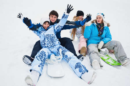 timbering: Four snowborders sit on snow and preparing to ride from the hill Stock Photo