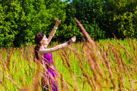Girl in violet dress on high grass meadow Stock Photo - 8593203
