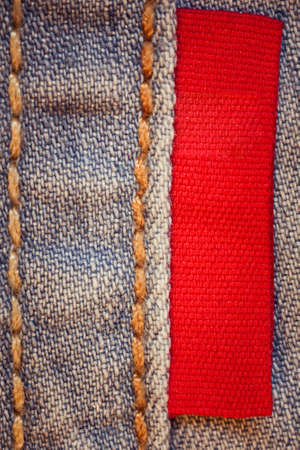 Blue jeans with empty red label close-up photo