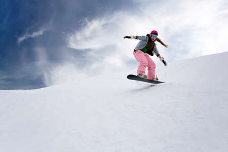 Girl rider jump on snowboard in mountains