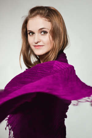 Portrait of young girl enveloped into violet scarf in profile photo
