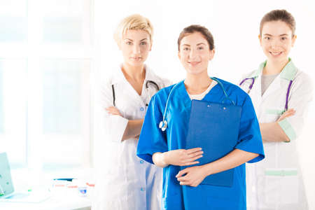 assistent: Nurse and two young doctors near the hospital window Stock Photo
