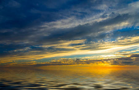 Incredible sunset, calm water and the sun, which setting in thunderclouds photo