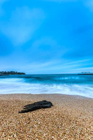 beach shingle: Solitaria spiaggia di ciottoli e mare spumoso dopo il tramonto