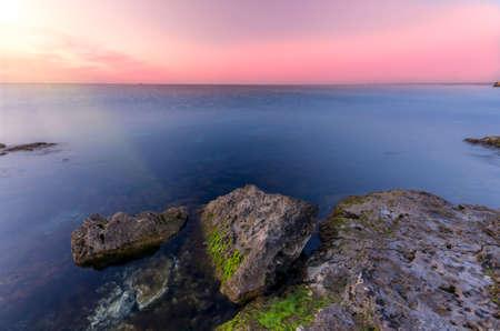 lovely sunset, overlooking sharp rocky shore of the ocean photo
