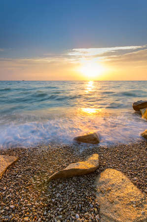 water stone: shrouded water stone on the pebble beach at sunset Stock Photo