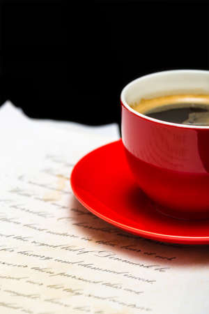 manuscript: Red cup of espresso coffee and paper manuscript on black background