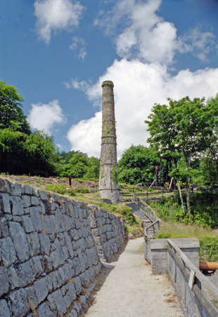 kaolin: An old china clay works chimney under a blue sky in cornwall Stock Photo