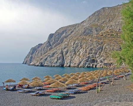 The Headland of Kamari Beach Santorini with thatched umbrellas
