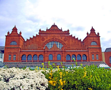 The ornate red brick facade of the Winter Gardens Theatre in Morecambe Lancashire under a blue sky with  flowers in front