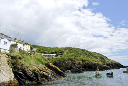 The Peaceful Cornish Harbour of Portloe with Fishing Boats under a blue sky