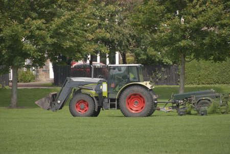 mowing grass: A Tractor Mowing Grass in a Park Stock Photo