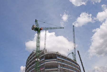 Two Tower Cranes on top of a new construction site lifting steel