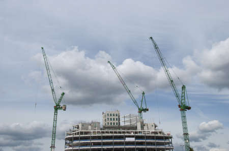Three Green Tower Cranes a building under construction Stock Photo - 10331689