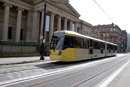 tramcar: A Modern Yellow Tramcar passing an old Art Gallery in a city street Editorial
