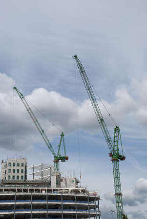 Two Green Tower Cranes a building under construction Stock Photo - 10331690