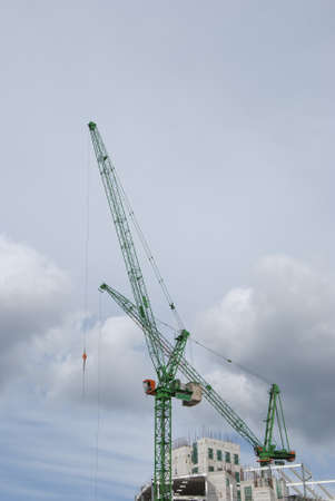 Two Green Tower Cranes a building under construction Stock Photo - 10331688