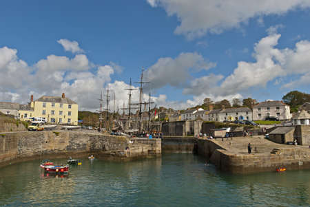 The Historic Harbour of Charlestown in Cornwall under a blue sky with tall ships Stock Photo