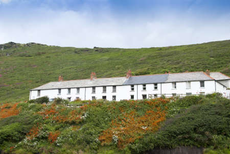 Seaside Cottages in Cornwall England on a hillside with orange crocosmia flowers photo