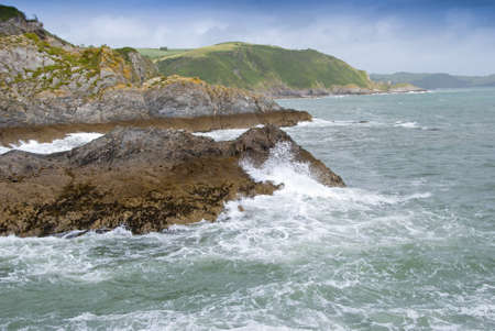 Waves Breaking on a rocky headland in Cornwall England Stock Photo