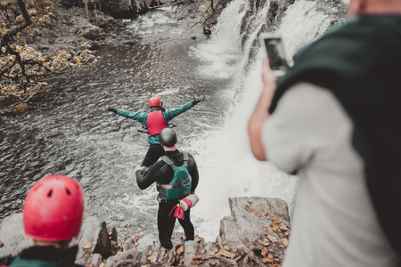 Coasteering in Wales - man jumping from the cliff into a waterfall