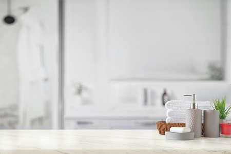 Bouteille en céramique grise avec des serviettes en coton blanc dans un panier sur un comptoir en marbre sur fond de salle de bain