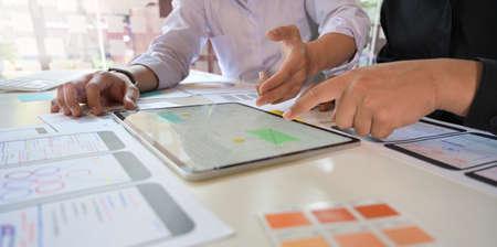 UX Designer team sketch mobile app developer outlines an app on tablet for web mobile smart phone