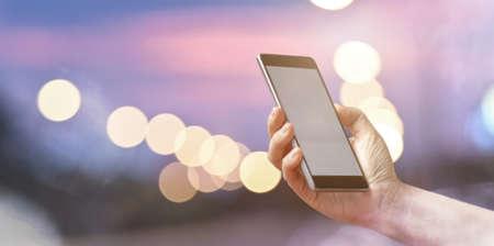 Mano femminile del primo piano che tiene lo Smart Phone mobile sopra il bokeh leggero