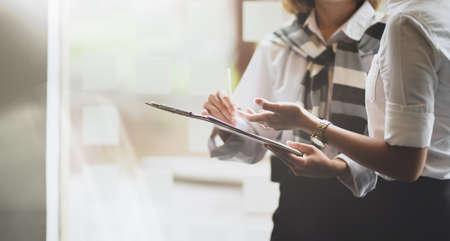 Junge Geschäftsfrauen diskutieren gemeinsam über das Unternehmensprojekt, während sie das Tablet halten Standard-Bild
