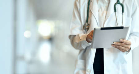 Close-up of young professional doctor summarising the patient chart with tablet in hospital