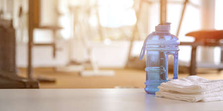 Towels and sport bottle with copy space blurred gym background Reklamní fotografie