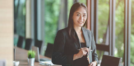 Beautiful Asian businesswoman confidently smile to the camera in meeting room