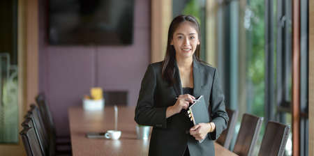 Beautiful young asian businesswoman smiling and looking at the camera in the meeting room Banco de Imagens