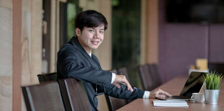 Attractive young asian businessman smiling and looking at the camera in the meeting room Banco de Imagens